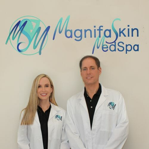 owners tony cucuzella and christina buckley under the magnifaskin medspa sign in wilmington delaware