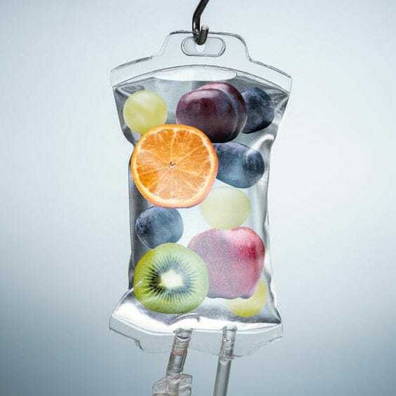 Close-up Of A Different Fruit Slices Inside Saline Bag Hanging With Hook In Hospital